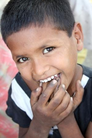A portrait of a shy poor kid from India putting dirty fingers in his mouth.